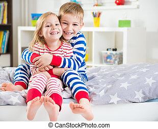 Two happy siblings in sleepwears in bed