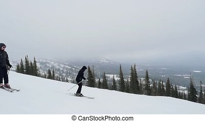 Two happy skiers on the slope at a ski resort in the mountains in slow motion.