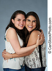 Two happy smiling latino girls hugging on gray studio background