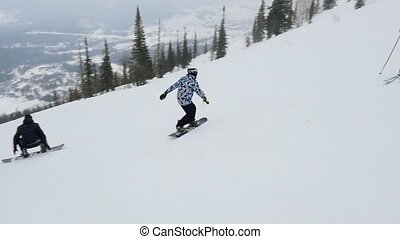 Two happy snowboarders and skiers on the slope at a ski resort in slowmotion. 1920x1080