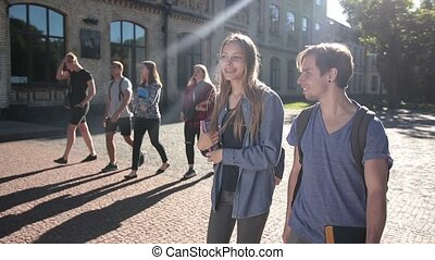 Two happy students walking on university campus