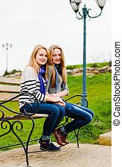 Two happy teen girls friends having fun outdoors