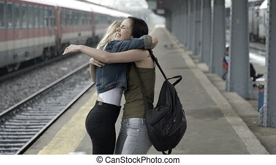 Two happy teen girls reunited in train station hugging and walking home hand in hand