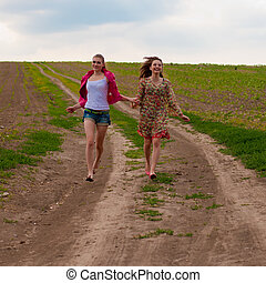 Two happy teen girls running