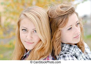 Two happy teen school girls friends outdoors