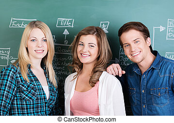 Two happy teenage girls and a boy in class posing together...