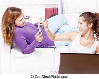 Two happy teenage girls having fun using electronic gadgets