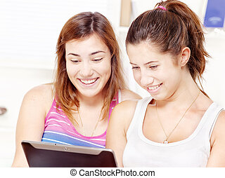 Two happy teenage girls using touchpad computer
