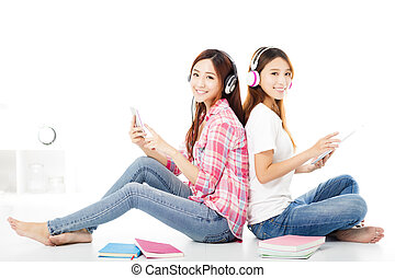 Two  happy teenage students girls sitting on the floor