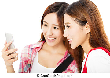 Two  happy teenage students girls watching the smart phone