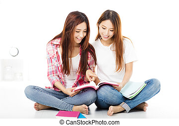 Two  happy teenage students girls watching the books