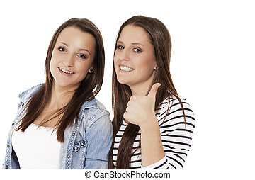 two happy teenager showing thumbs up on white background