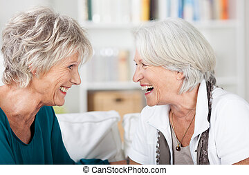 Two happy woman enjoy a laugh together