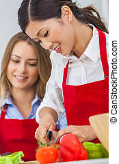 Two Happy Women Cooking Preparing Food in a Kitchen