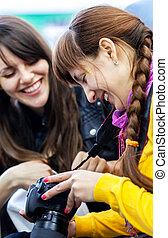 Two happy women friends looking at photos on digital camera