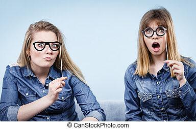 Two happy women holding fake eyeglasses on stick