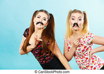Two happy women holding fake moustache on stick