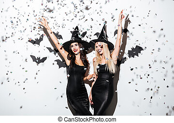 Two happy women in black witch halloween costumes on party...