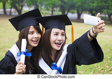 Two happy women in graduation gowns taking picture with cell pho