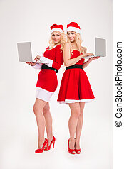 Two happy women in santa cloth using laptop computer