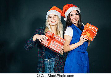Two happy women in santa hats with gift boxes standing