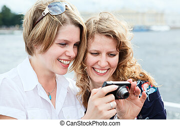Two happy women looking at screen of simple hand-held camera
