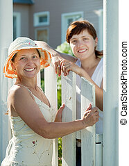 happy women near fence wicket - Two happy women near fence...