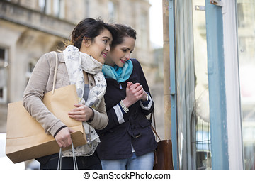 Two happy women shopping together, having fun and laughing