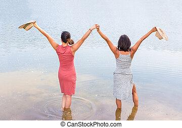 Two happy women standing in water