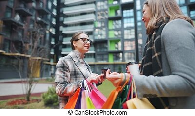 Two happy women standing with shopping bags and takeaway coffee and talk with interest among themselves after successful shopping. Modern buildings on background