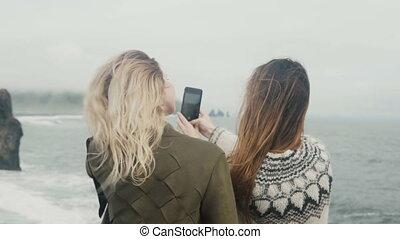 Two happy women taking selfie photos on smartphone, girls...