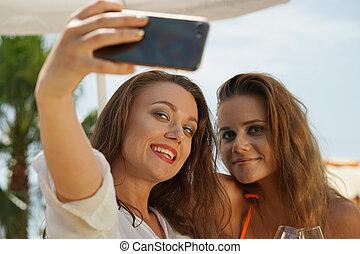 Two happy women taking selfie