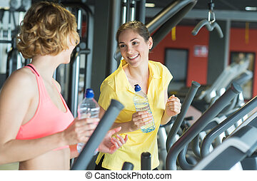 two happy women with bottles of water talking in gym