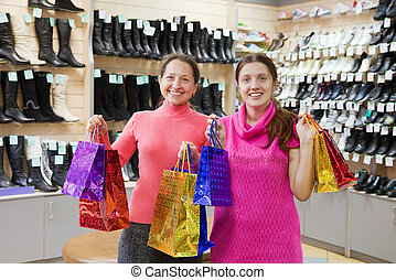 women with shopping bags at shoes shop