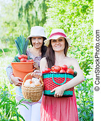 Two happy women with   vegetables