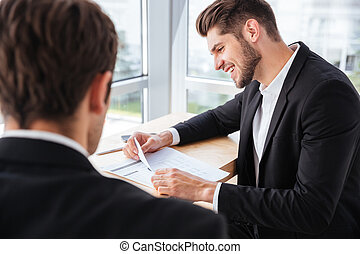 Two happy young businessmen discussing business plan together