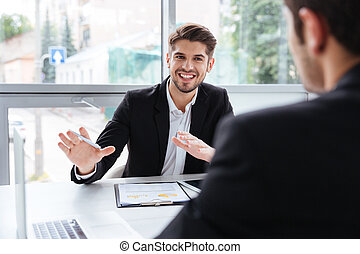 Two happy young businessmen sitting and working on business meeting