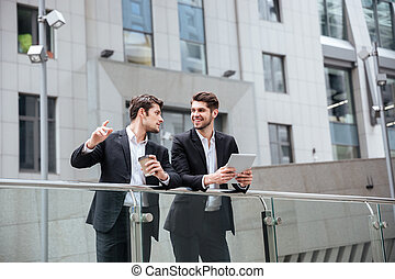 Two happy young businessmen with tablet standing and talking