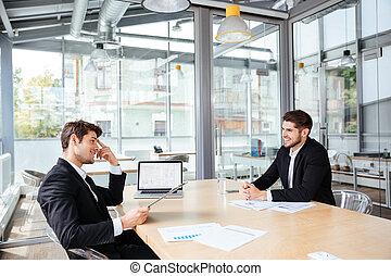 Two happy young businessmen working together on business meeting