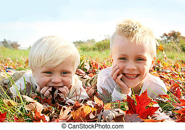 Two Happy Young Children Playing Outside in Fall Leaves