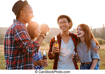Two happy young couples drinking beer and soda together