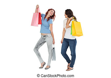 Two happy young female friends with shopping bags - Full...