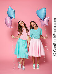 Two happy young girls dressed in bright colorful clothes