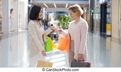 Two happy young girls meet with a hug in a department store...