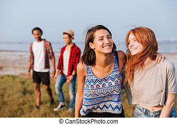 Two happy young men and women walking outdoors