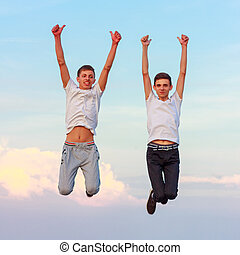 two happy young men jumping up on the nature
