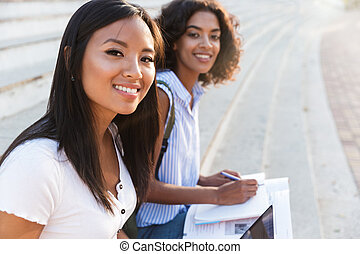 Two happy young students girls studying