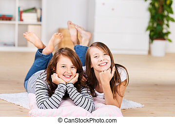 Two happy young teenage girls laying on the floor