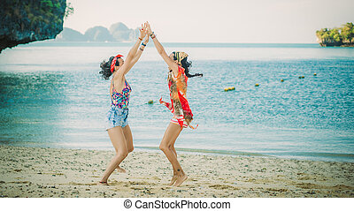 Two happy young woman jumping and laughing on the beach....