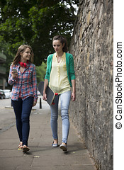 Two happy young woman walking outdoors.